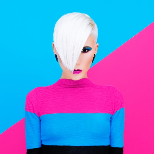 Fashion blond model with trendy hairstyle on a colorful background. Art photo